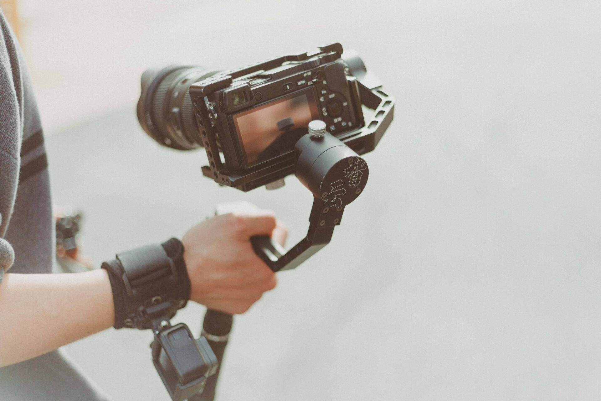 person holding black dslr camera for video production